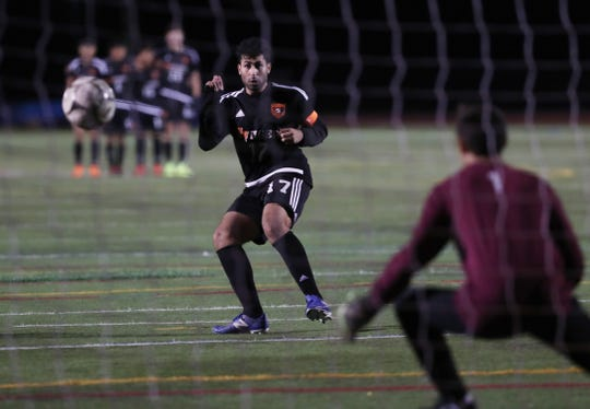 From left, White Plains' Alexander Sagnibene (17) gets a penalty kick past Scarsdale goalie Luca Schettino (1) during boys soccer playoff action at White Plains High School Oct. 24, 2019. White Plains won the game 4-1 in PKs.