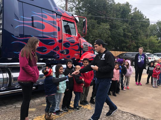 Joe Fiduccia hands out anti-bullying stickers to Fain Elementary students Friday.  He built an Optimus Prime replica over the course of one year. The truck will be on display at the Wichita Falls Comic Expo this weekend at the MPEC.
