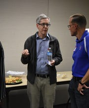 Dale Raines, pictured left, speaks with members of the public following the Zanesville Think Tank on Poverty Candidate's Forum.