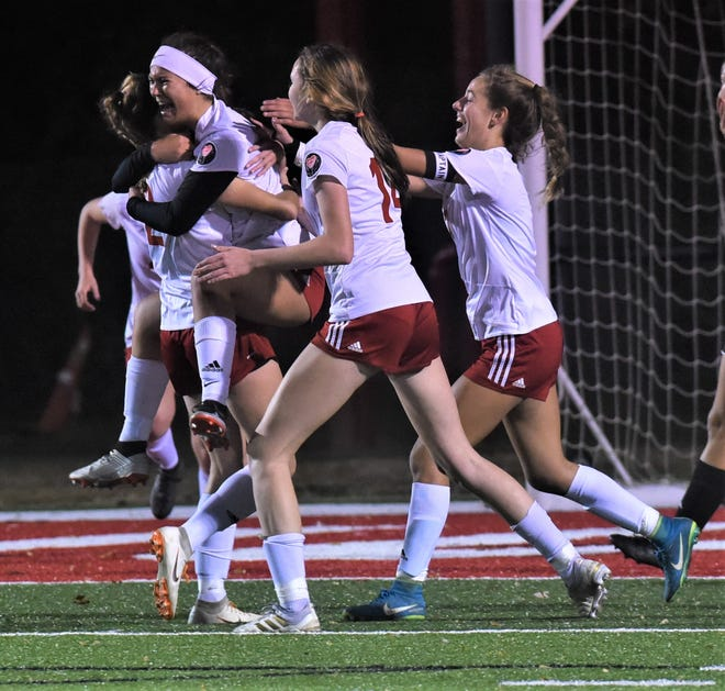 Rosecrans sophomore Parker Farrell (white headband) celebrates her goal with her teammates on Thursday. The Bishops won their sixth straight district title by a 1-0 score over Berlin Hiland.