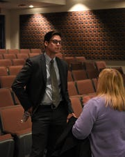 Andrew Body, pictured left, speaks with members of the public following the Zanesville Think Tank on Poverty Candidate's Forum.