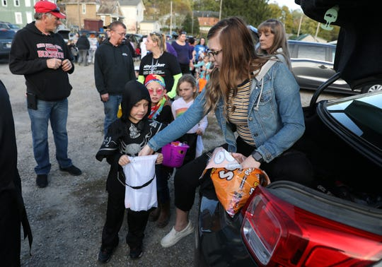 Alyssa Smith hands out candy from the trunk of a car during Eastside Community Ministries trunk-or-treat event last week. Zanesville, South Zanesville and many surrounding communities will have trick-or-treating on Thursday evening.