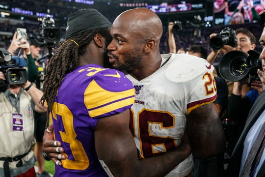 Washington Redskins running back Adrian Peterson (26) talks with Minnesota Vikings running back Dalvin Cook (33) following the game at U.S. Bank Stadium.