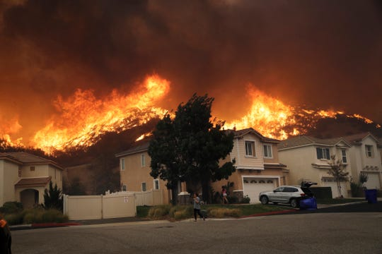 A wildfire approaches a residential subdivision on Oct. 24, 2019, in Santa Clarita, Calif.