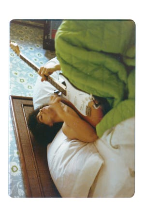 Prince plays a guitar in bed at his new home on France Avenue, April 1978.