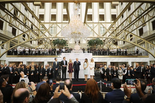 Republican presidential nominee Donald Trump and his family, from left, son Donald Trump Jr, son Eric Trump, wife Melania Trump and daughters Tiffany Trump and Ivanka Trump prepare to cut the ribbon at the new Trump International Hotel Oct. 26, 2016 in Washington, DC. The hotel, built inside the historic Old Post Office, has 263 luxury rooms, including the 6,300-square-foot 'Trump Townhouse' at $100,000 a night, with a five-night minimum. The Trump Organization was granted a 60-year lease to the historic building by the federal government before the billionaire New York real estate mogul announced his intent to run for president.