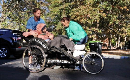 Joe Rooney and Christine Nichols help get Mikey Nichols into his racing wheelchair for one of their regular workouts as they prepare for the NYC Marathon.