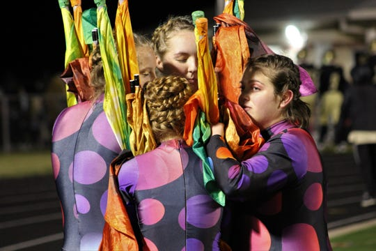 Clyde High School color guard members huddle for a prayer before their halftime performance Friday at Bulldog Stadium, and perhaps for warmth, too, on a chilly evening. They, along with the members of the Bulldog Band, will perform in San Antonio Wednesday, Nov. 6.
