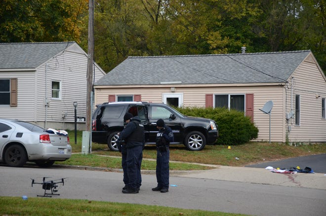 Police collect evidence at the scene of the Saturday morning shooting.