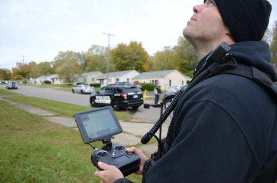 Officer Andrew Olsen from the Battle Creek Police Department Crime Lab flies a drone to photograph the scene of the shooting.