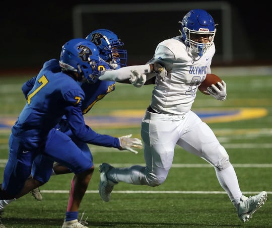 Bremerton's Willis C Newman (7) and Kanye Taylor (10) chase down Olympic's Cameron Bailey (21) during the first half of their game on Friday, October 25, 2019.