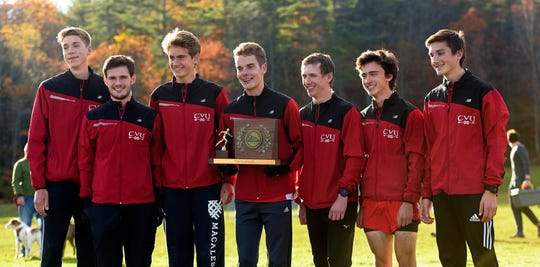 From left, Drew Buley, Gavin Schaaf, Matthew Servin, Parker Soares, Caleb Nye, Skyler Heninger and Matthew Ireland collect the Division I championship trophy at the Vermont State Cross Country Meet at Thetford Academy on Saturday, Oct. 26, 2019. The Redhawks beat Essex, 46-73.