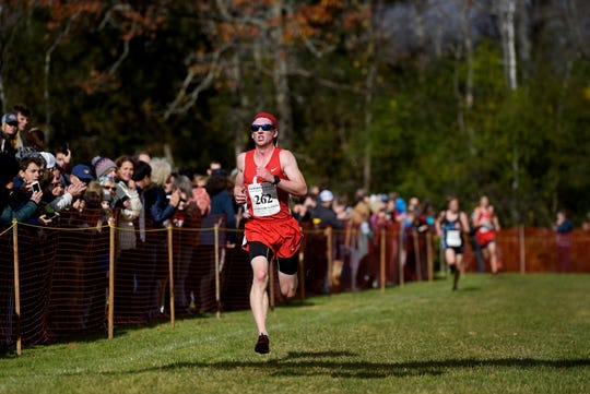CVU's Caleb Nye crosses the finish line during the Division I championship at the Vermont State Cross Country Meet at Thetford Academy on Saturday, Oct. 26, 2019. The Redhawks won the team title over Essex, 46-73.