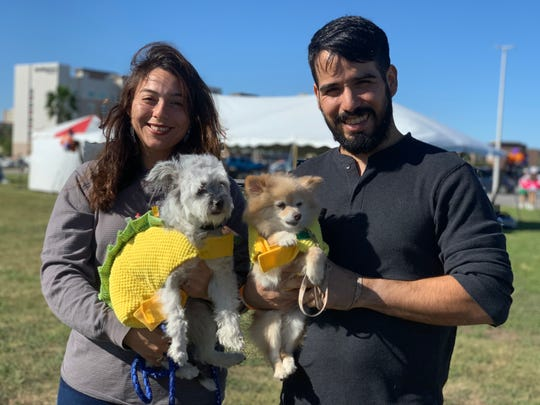Stephanie Chavez and Chris Delgado pose with Domino (left) and Candy (right), who are dressed as tacos, at the Thomas J. Henry's eighth annual Bark in the Park at Water's Edge Park on Saturday, Oct. 26, 2019.