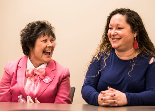 Brenda Burgett, left, and Laura Potter take a quick moment to laugh as they buck the stereotypes of society by agreeing that femininity isn't defined by hair or breasts.
