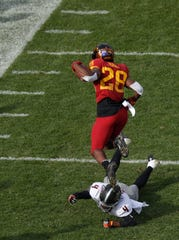 Oklahoma State cornerback A.J. Green, bottom, trips up Iowa State running back Breece Hall during the first half of an NCAA college football game, Saturday, Oct. 26, 2019, in Ames, Iowa.