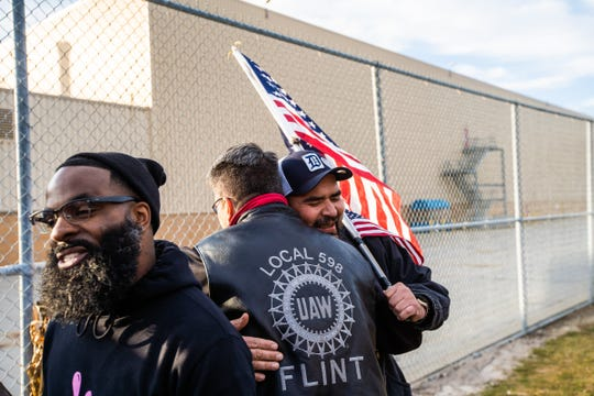 Flint Assembly Electrician Mike Perez (right) celebrates with others outside of Flint Assembly after UAW ratified their contract with General Motors marking the end of the strike on Friday, October 25, 2019.