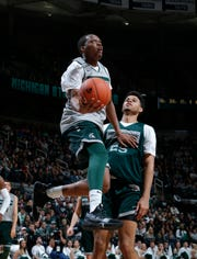 Michigan State's Cassius Winston, left, puts up a scoop shot against Malik Hall during the NCAA college basketball team's scrimmage Friday, Oct. 25, 2019, in East Lansing.