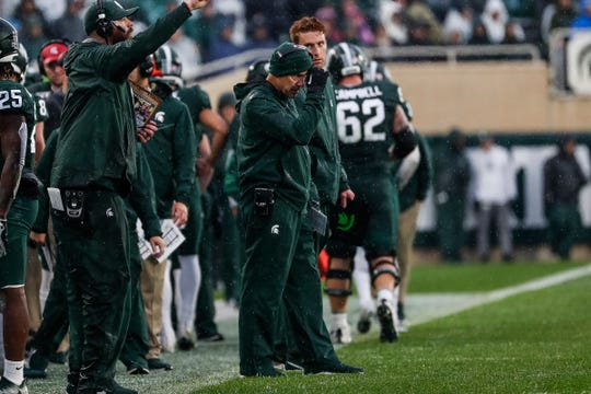 Michigan State coach Mark Dantonio adjusts his hat in the rain during a timeout in the first half at Spartan Stadium in East Lansing, Saturday, Oct. 26, 2019.