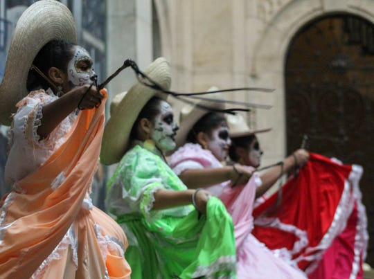 Dancers swing whips as part of a performance by Ballet Folklorico De Detroit at the Detroit Institute of Arts, Saturday, Oct. 26, 2019.