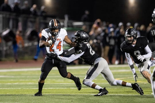 Belleville running back Kobe Langford (24) runs against Plymouth defensive line Caleb Sadler (24) during the first half at Plymouth-Canton Educational Park in Canton, Friday, Oct. 25, 2019.