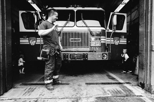"A Fire Department New York firefighter from Rescue Company II firehouse in Brooklyn, N.Y.  waves at a young child.  The photo is part of  the ""Rescue 2: Before the Call"" black-and-white photo  exhibit taken by Detroit Lions defensive end Romeo Okwara."