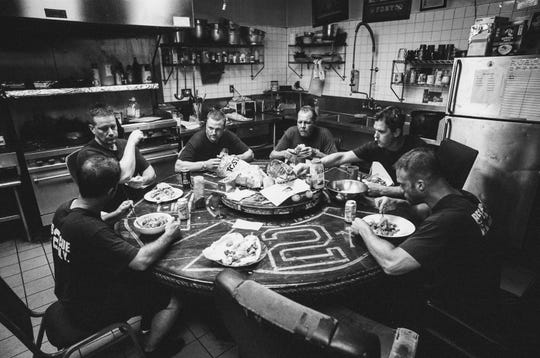 "Fire Department New York firefighters from Rescue Company II firehouse in Brooklyn, N.Y., eat a meal together. The photo is part of  the ""Rescue 2: Before the Call"" black-and-white photo  exhibit taken by Detroit Lions defensive end Romeo Okwara."