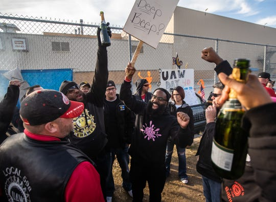 UAW Local 598 Alternate Committee Rep Will McIntosh (center left) and Alternate Committee rep Stanley Dulaney throw their hands in the air as they celebrated outside Flint Assembly after UAW ratified their contract with General Motors which marked the end of the strike Friday 25. October 2019.