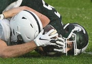 Penn State's Dan Chisena, left, recovers a fumbled punt by Spartans' Brandon Sowards, right, early in the third quarter.
