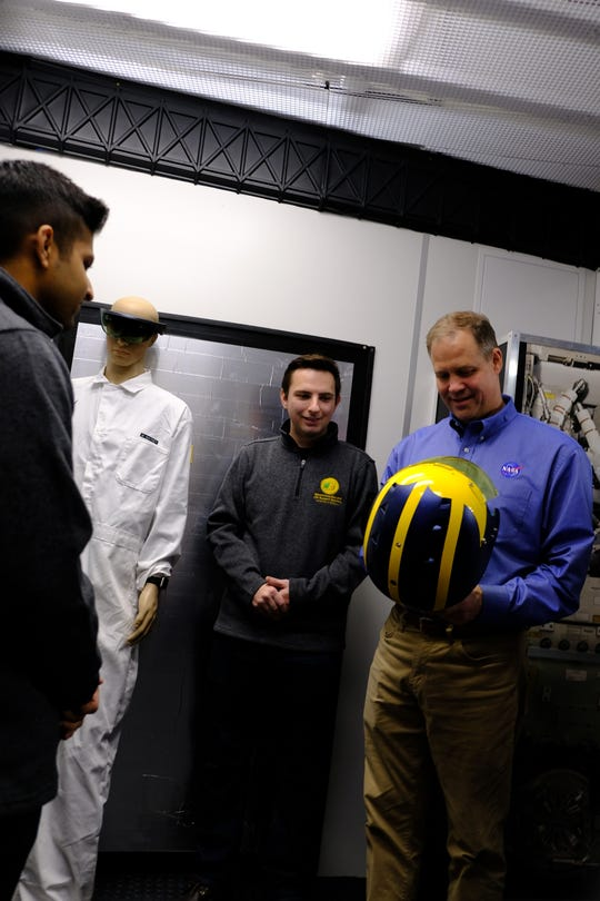 NASA Administrator Jim Bridenstine holds a UM football helmet in front of one of the past researchers who also studied space exploration at the university.