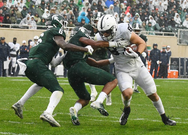Penn State's Pat Freiermuth plows through Michigan State's David Dowell and Xavier Henderson after a reception and goes into the end zone for a touchdown in the second quarter.
