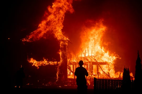 FILE - In this Nov. 8, 2018 file photo a home burns as the Camp Fire rages through Paradise, Calif. As California counties face the prospect of increased utility power shut-off meant to prevent wildfires, counties with more resources are adapting much more easily to the challenge than poorer ones.