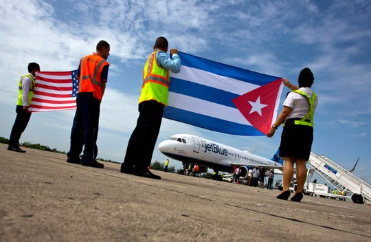 FILE - In this Aug. 31, 2016 file photo, airport workers receive JetBlue flight 387, the first commercial flight between the U.S. and Cuba in more than a half century, holding a United States, and a Cuban national flag, on the airport tarmac in Santa Clara, Cuba. The Trump administration is banning U.S. flights to all Cuban cities except Havana starting in December 2019.