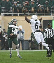 MSU's Brian Lewerke throws over Penn State's Cam Brown in the first quarter.