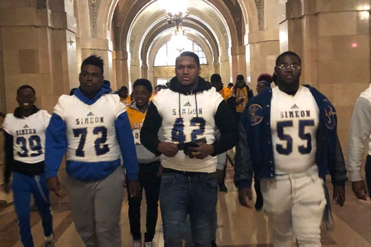 George Robinson (72) and Ronald Haggins (42) with members of the Simeon High School football team appear at City Hall Friday, Oct. 25, 2019, shows in Chicago.