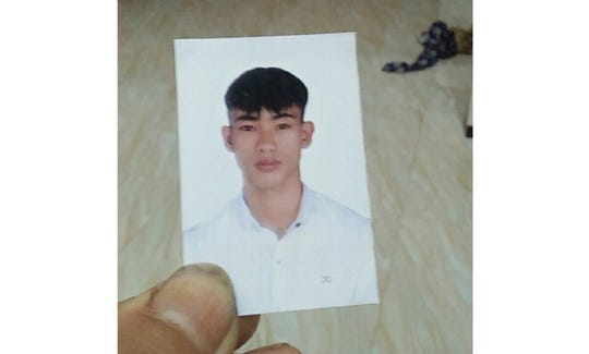 Nguyen Dinh Hai holds an ID photo of his younger brother Nguyen Dinh Luong, 20, at his home on Oct. 26, 2019, in Can Loc district, Ha Tinh province, Vietnam. Luong's family fears that he may be among the 39 people found dead in the back of a container truck in southeastern England. (Nguyen Dinh Hai via AP Photo)