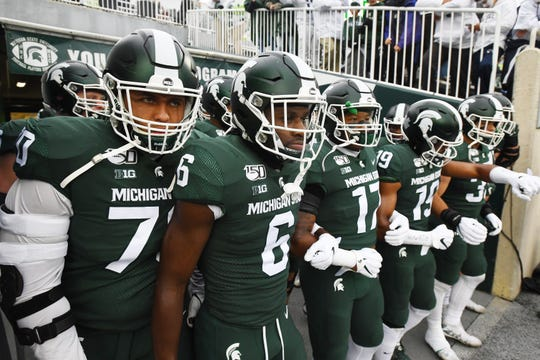 Tyler Higby, David Dowell and the Michigan State Spartans prepare to head onto the field for the game against Penn State.