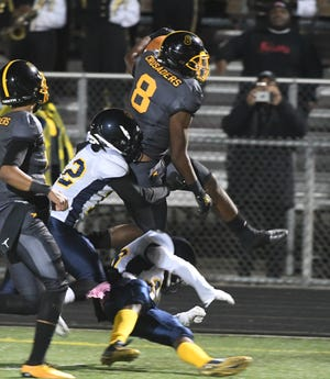 Detroit King running back Peny Boone leaps over a Detroit Denby defender on a run during the first quarter on Friday.