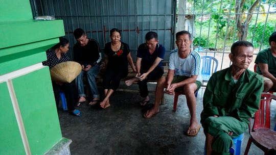 Relatives and neighbors of Bui Thi Nhung sit outside her family home in Do Thanh village in Vietnam, Saturday Oct. 26, 2019. Family members fear that Nhung could be among the dozens of people found dead in the back of a truck in southern England. (AP Photo/Linh Do)