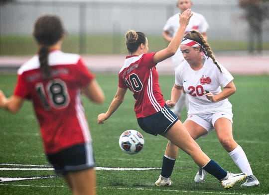 Mater Dei's Emma Peerman (20) pushes the ball past defense from South Dearborn's Katie Cutter (10) as the Mater Dei Wildcats play the South Dearborn Knights in the IHSAA soccer semi-state Saturday afternoon at Bundrant Stadium, October 26, 2019.