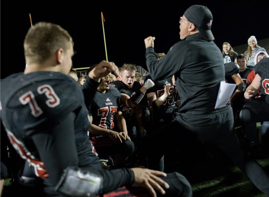 Southridge assistant coach Kelly Murphy celebrates with the Raiders following Friday's 43-14 sectional victory over Mount Vernon.