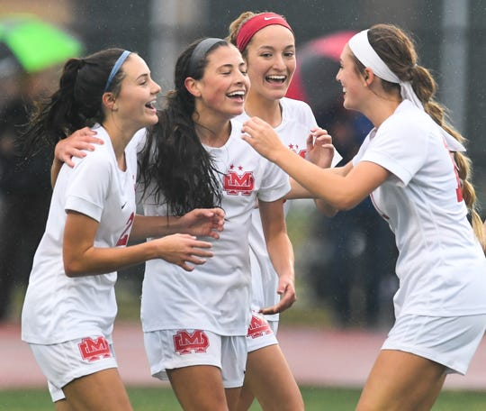 Mater Dei's Ellsa Bonnell (1), surrounded by her sister Mater Dei's Este Bonnell (2) and teammates, celebrate her score in the first period making it 2-0 as the Mater Dei Wildcats play the South Dearborn Knights in the IHSAA soccer semi-state Saturday afternoon at Bundrant Stadium, October 26, 2019.
