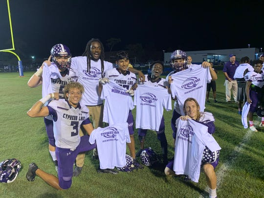 Cypress Lake celebrates with their pre-made t-shirts after a 44-7 win over DeSoto County in the district championship.