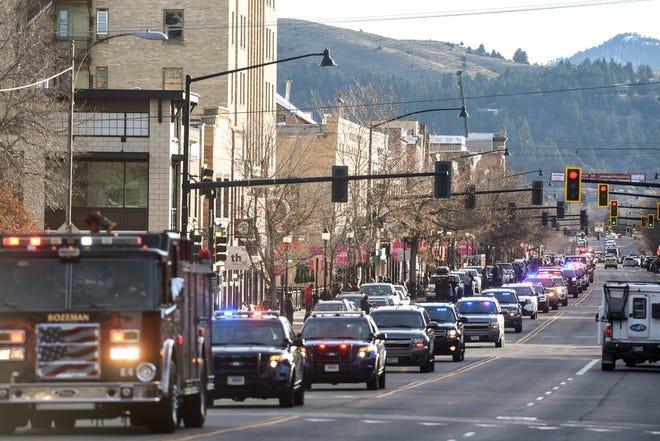 Hundreds of law enforcement vehicles stream through downtown Bozeman, Mont., in honor of Deputy Jake Allmendinger on Friday, Oct. 25, 2019. (Rachel Leathe/Bozeman Daily Chronicle via AP)