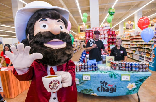 Janice Crisostomo wears a Mr. Brown mascot costume as she and other Lucky Supplies employees, Joshua Ahn and Sonia Raqueno, offer free coffee sample to shoppers during the grand opening of Pay-Less Supermarket's newest store in Maite on Saturday, Oct. 26, 2019.