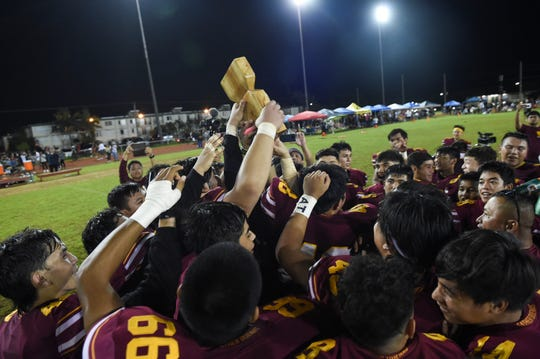 The Father Duenas Friars raise their IIAAG High School Football championship trophy at the George Washington High School Field in Mangilao, Oct. 26, 2019. The Friars defended their football title against the George Washington Geckos for the fifth straight year.
