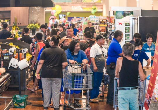 Customers shop in Pay-Less Supermarket's newest store in Maite after a blessing and ribbon cutting was held to celebrate its official grand opening on Saturday, Oct. 26, 2019.