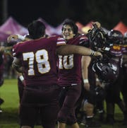Father Duenas quarterback Nicholas Anderson (10) celebrates with teammate Aidan Bordallo (78) after beating the George Washington Geckos in their championship game in Mangilao, Oct. 26, 2019.