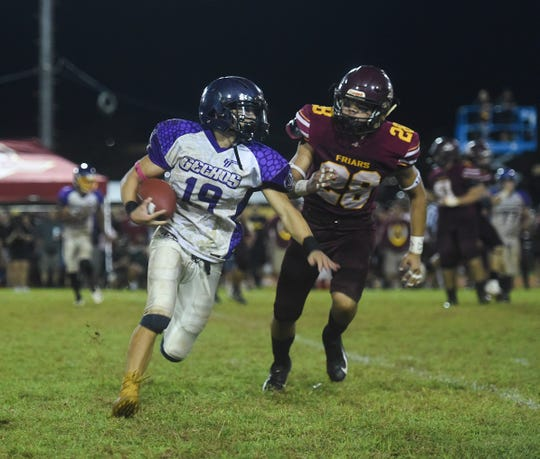 George Washington running back Eian Naputi (19) attempts to lose a Father Duenas defender during the IIAAG High School Football championship game Saturday. Although the Department of Education will be running its own sports league beginning in January, Superintendent Jon Fernandez has invited the IIAAG to compete in inter-league play for third and fourth quarter sports.