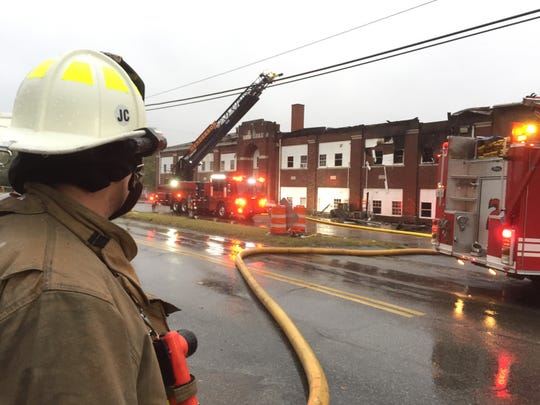 Henderson Fire Chief Scott Foreman surveys the scene early Saturday morning as crews wrap up operations at the Weaverton School building, which has been serving as an apartment building.